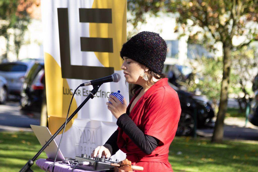 A cantora Telma Pereira apresenta o projeto TRAMA no Hospital Pulido Valente, em Lisboa. Telma veste roupa vermelha, com mangas pretas e uma touca preta. A cantora segura uma caixinha de música e canta ao microfone. Ao fundo, vê-se o banner do Lugar Específico.