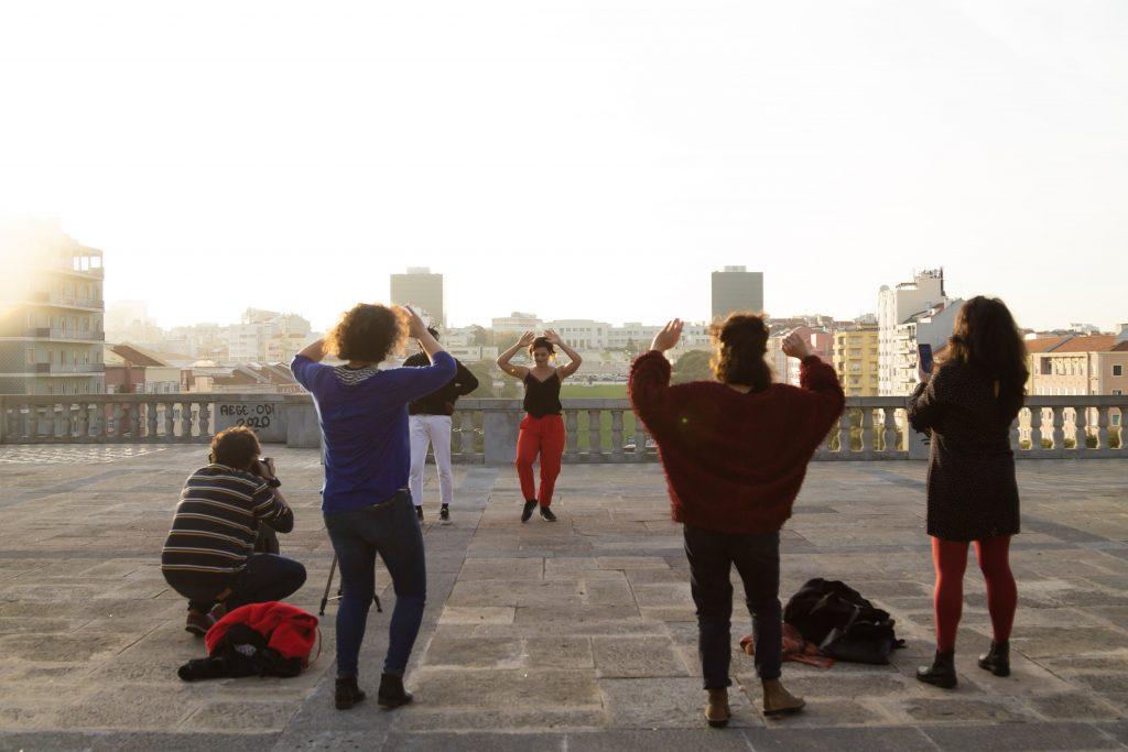 Os artistas Maria Antunes e Sango em apresentação ao ar livre em Lisboa. Três mulheres repetem a coreografia que os bailarinos propõem e um homem faz a filmagem.